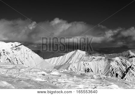 Black And White View On Ski Slope And Beautiful Snowy Mountains In Clouds