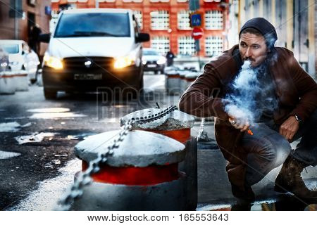 Man smokes an electronic cigarette on the streets of a big city.