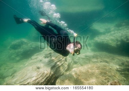 Silhouette of a free diver, green background