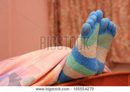 Feet with striped socks finger in bed
