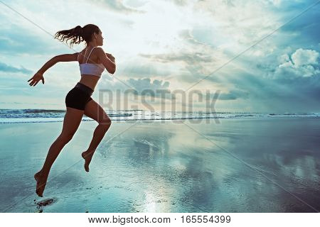 Active sporty woman run along ocean surf by water pool to keep fit and health. Sunset black sand beach background with sun. Woman fitness jogging workout and sport activity on summer family holiday.