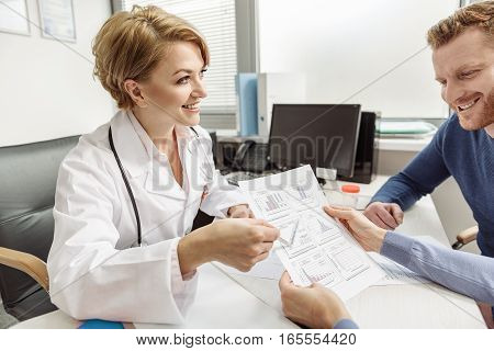 Cheerful doctor is sitting near table. She looking at patients and paying attention to sheet of paper with diagrams