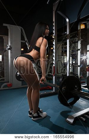 Muscular woman in a gym doing heavy weight exercises. Young girl doing weight lifting at health club. Strong female at gym.
