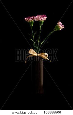 Flowers in a vase. Flowers of carnations. Ceramic Vase. Color photography on a black background.