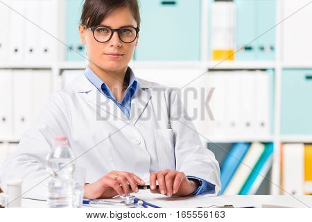 Thoughtful Female Doctor Sat At Desk
