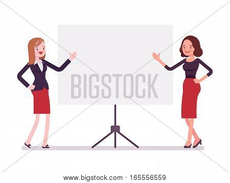 Young attractive smiling businesswomen near the standing presentation display board, pointing with hands, good equipment for projects, confident speakers, full length, copy space