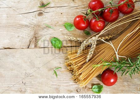 Ingredients for an Italian pasta meal with wholemeal spaghetti wheat ears tomatoes and basil herbs as seen from above on a rustic wooden background generous copy space