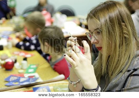 Girl paints Christmas toy at table in class