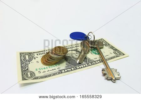 House key over the hundred dollar banknotes isolated on white background. Ideal for realtors