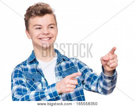 Emotional portrait of caucasian teen boy. Funny teenager pointing and looking away while laughing, isolated on white background. Handsome happy child pointing at copy space.