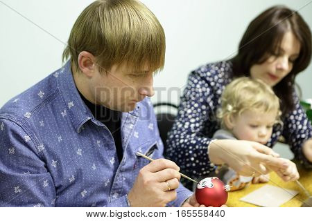 Man painting Christmas ball at table in class
