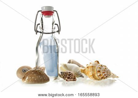 message in a bottle made of glass between some sea shells isolated on a white background
