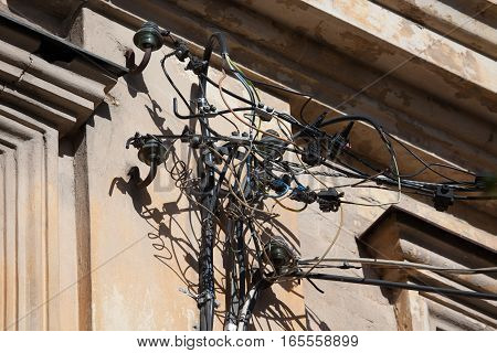 Dangerous installation of electricity cables and wires on the wall of an old building