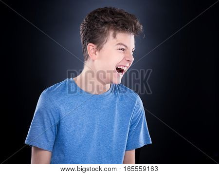 Emotional portrait of irritated shouting teen boy. Furious teenager screaming and looking with anger away. Handsome outraged child shouting out loud, on black background.