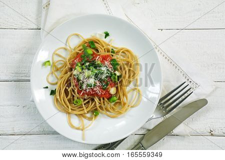 wholegrain spaghetti with fresh tomato sauce and scallions seen from above on a white rustic wooden background with copy space homemade vegetarian pasta in Mediterranean style