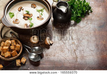 Mushroom cream soup with croutons and fresh parsley on a old wooden table with copy space.