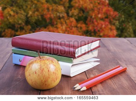 stack of book pencils and yellow apple. Against the background of autumn leaves