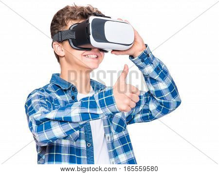 Happy teen boy wearing virtual reality goggles watching movies or playing video games, on white. Cheerful smiling looking in VR glasses and making thumb up gesture. Child experiencing virtual reality.