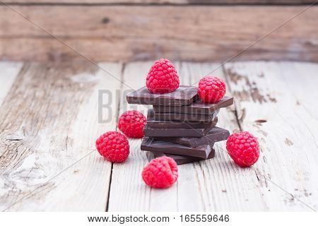 Dark chocolate stack with fresh raspberries, on wooden table. Natural light, selective focus.