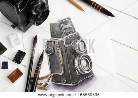 Watercolor sketch of retro camera vintage photo camera paintbrushes and watercolor paints. Flat lay top view.