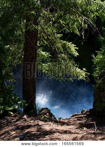 The wild waters and spray from the bottom of Koosah Falls on the McKenzie River in the Willamette National Forest in Western Oregon framed by fir trees and a cliff on a summer day.
