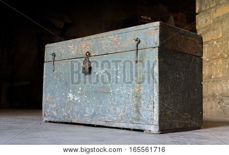 Old wooden toolbox, closed with a padlock, timeworn paint
