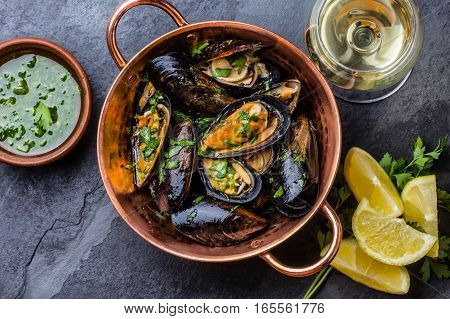 Shellfish Mussels in copper bowl with lemon and herbs sauce and white wine. seafood. Top view