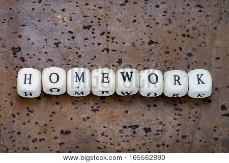 Homework word on wooden cubes on a brown cork background