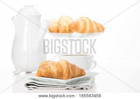 Fresh buttery croissants served with a cup of coffee.