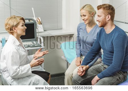 Smiling confident gynecologist is sitting afore happy couple in room with ultrasound equipment. She telling them important information