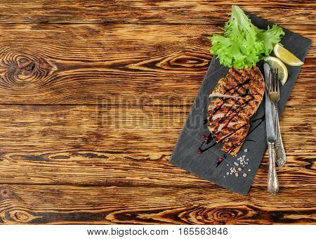 Grilled Chicken Fillet With Spices, Sliced And Served With Lemon And Salad Leaves. Selective Focus.