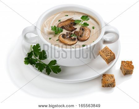 Mushroom cream soup decorated with sliced champignons parsley and croutons in a white ceramic bowl. Isolated on white background.