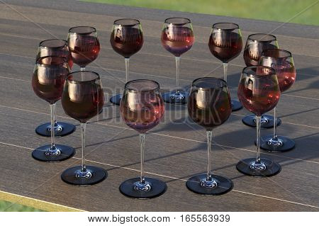 Tasting with circle of glasses with red and roze wine on the wooden table. 3d render