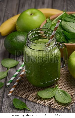 Green smoothie with apple, banana, avocado and spinach on rustic  wooden background.