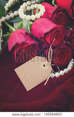fresh red roses on scarlet velvet background with jewels and empty tag, retro toned