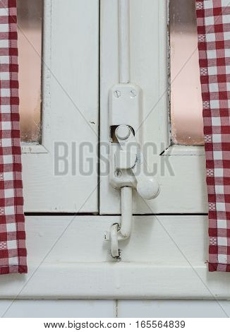 Old wooden window lock, painted covering wood, metal and screws. With Vintage curtain with red and white squared pattern
