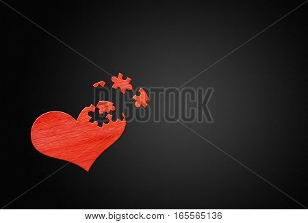 Red wooden puzzle heart on black wooden background
