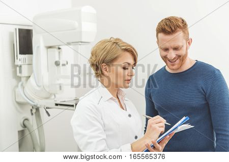 Assured doctor is standing beside happy male patient. She absorbedly writing