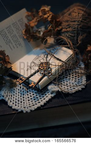 old retro styled composition of book, dried flowers, a tangle of old thread and the keys
