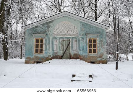 Abandoned house in the woods on the riverbank all covered with snow.