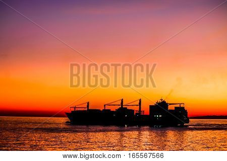 Big cargo ship silhouette leaving harbor during sunset.