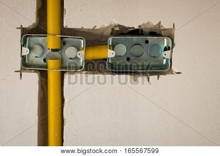 close up two steel box electric socket installation inside masonry wall at construction site
