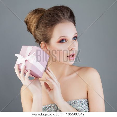Curious Woman Holding Gift Box with Silky Pink Ribbon. Surprise