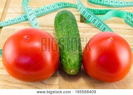 Cucumber and tomato with measuring tape over desk - the concept of dieting and health
