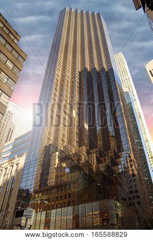 Tall skyscraper in New York city sunrise in background.