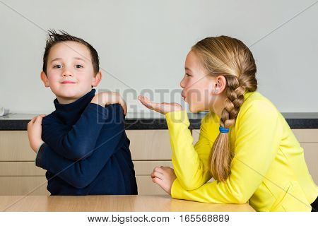 A pretty little girl blows a hand kiss to her cute brother at home in the kitchen