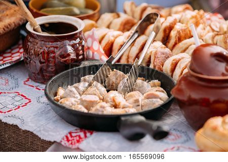 The dishes of the traditional Belarusian cuisine - fried bacon and meat sausages, pastries.