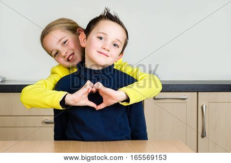 Little kids (siblings boy and girl) hug and girl forms heart with hands at home in the kitchen