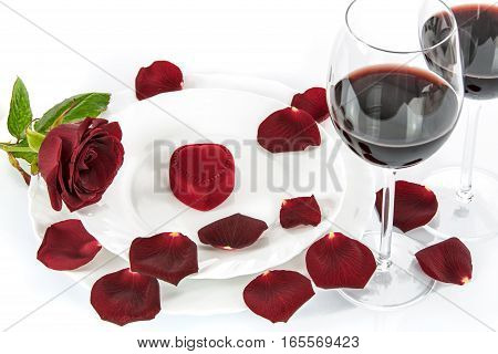 Table setting for a romantic Valentines Day dinner with a red rose red wine and gift.