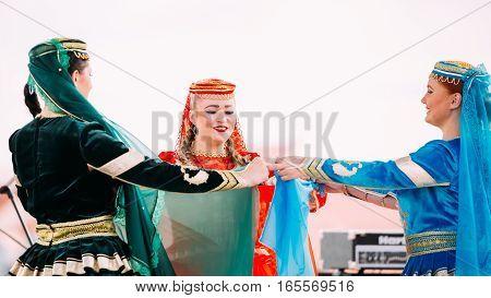 Minsk, Belarus - September 3, 2016: Young women dressed in traditional folk costumes dancing Azerbaijani folk dances.